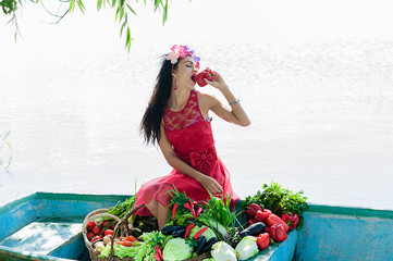 beautiful woman on the boat with vegetables eats pepper