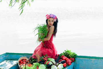 woman in red dress sitting in a boat with vegetables