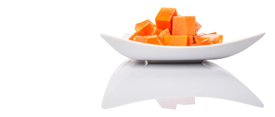 Bite sized papaya fruit on white plate over white background