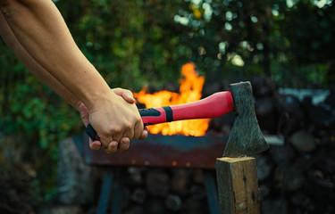 Мужчина колет дрова на фоне огня
