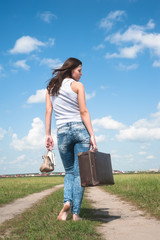 Pretty woman with old suitcase goes afar