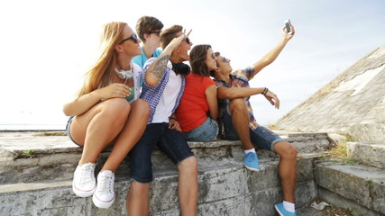 group of smiling teenagers making selfie outdoors