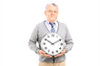 Senior gentleman holding a big wall clock