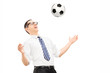 Young excited businessman playing with a soccer ball
