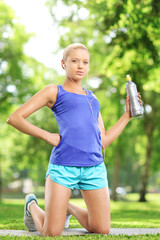 Female athlete holding a water bottle and resting in a park