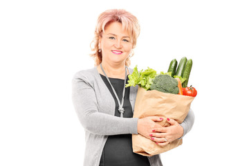 Mature lady holding a bag full of groceries