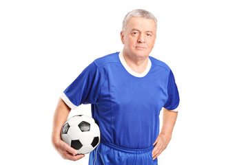 Mature man in sportswear holding a football