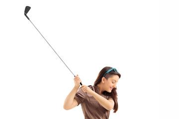 Profile shot of a woman swinging a golf club