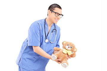 Young male doctor giving a teddy bear