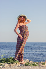 Beautiful pregnant woman relaxing near the sea