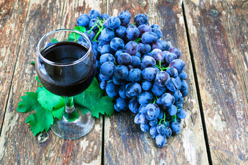Grapes on a old wooden table and a glass of red wine