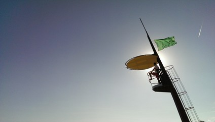 Lifeguard stands on the safety tower with green flag