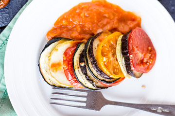 vegetable ratatouille on a plate with sauce, top view