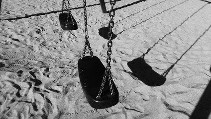 Empty swing with chains on sandy beach