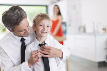 proud father helping his boy to put his tie