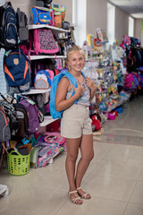 young girl in a supermarket buys a backpack.