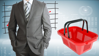 Businessman with shopping basket and graphs