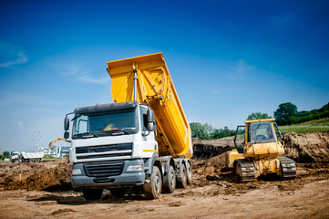 dumper truck and bulldozer at highway road construction site