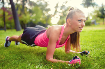 fitness woman stretching and working out in park, on grass