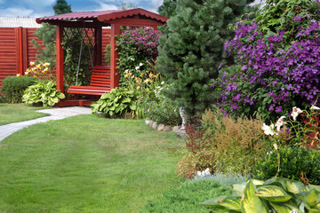 a cozy corner of the garden with a bench, lawn and flowering cle