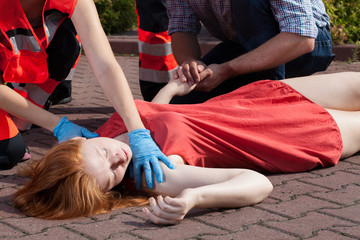 Paramedic helping unconscious woman