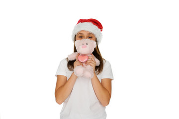 Young girl in a Santa hat with a teddy bear
