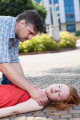 Man helping unconscious woman