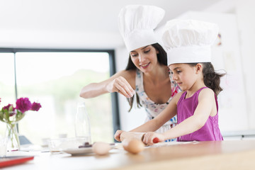 little girl helping her mother prepare a cake
