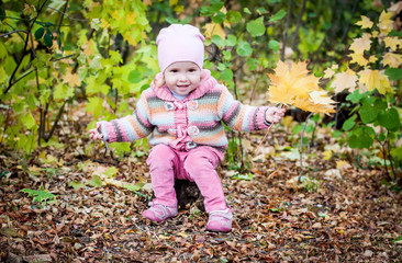 happy toddler girl gathers leaves