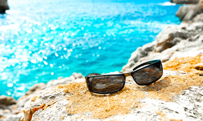 Sunglasses on a rock by the sea