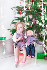 Cute laughing toddler girl and her little baby brother sitting t