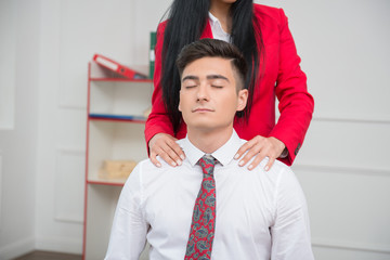 Woman doing massage to her colleague in office, relationship at