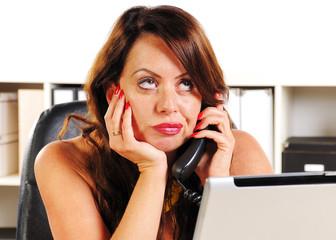 Sekretärin telefoniert genervt und sitzt hinter Computer