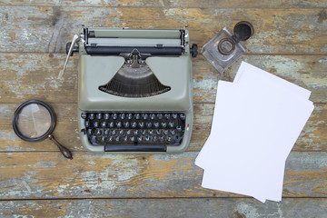 Vintage typewriter, inkwell, magnifier and the sheets of paper