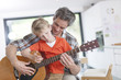 father learning his boy to play guitar - 69178877