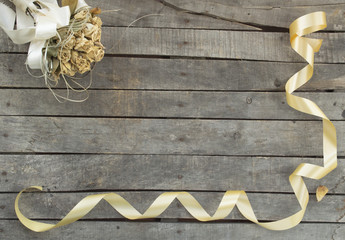 decorative ribbon and bouquet on wooden background