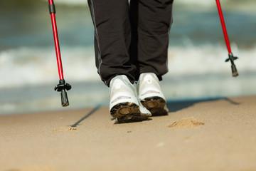 Nordic walking. Female legs hiking on the beach.
