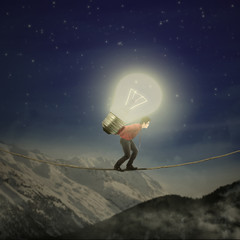 Businessman carrying bulb on the rope