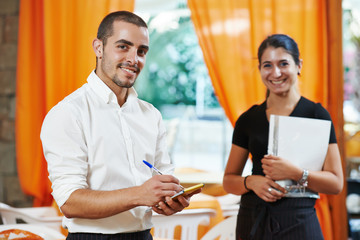 Waitress girl and waiter man in restaurant