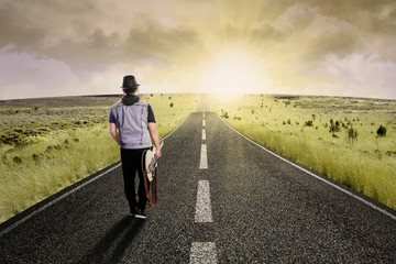 Lonely guitarist walking on road 1