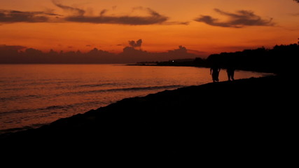 Two men jogging by the sea during sunset