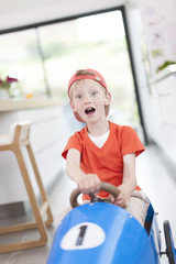 expressive boy playing with his pedal car at home