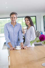 handsome couple is drinking tea and coffee at home