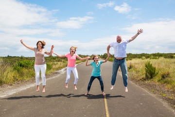 Family jumping together on the road