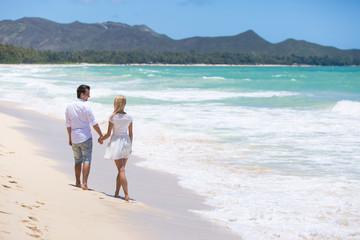 Happy couple walking on beach.