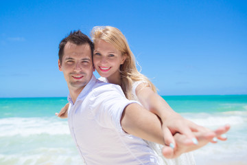 Cheerful couple having fun at the beach on a sunny day