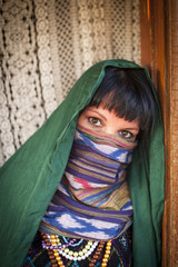 Portrait of young girl covers her face with a veil. Hijab.