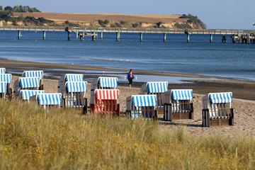 Frau spaziert zwischen Strandkörben, Ostsee