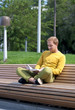 Man reading a book on a park bench