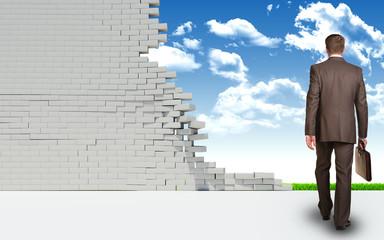 Businessman goes through ruined brick wall